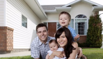 Couple with two kids playing in front yard of house