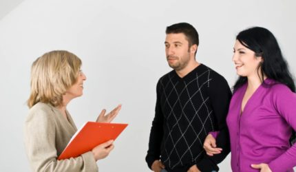 Woman holding clipboard talking to a couple